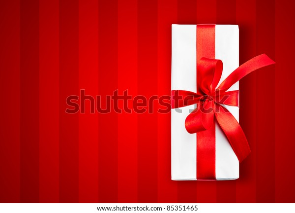 White box with a red ribbon on stripped background