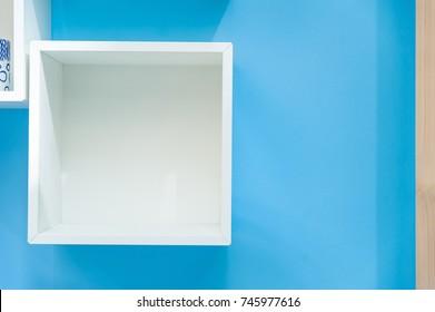 White box shelf isolated on blue background.Empty white shop shelf, retail shelf on blue vintage background.