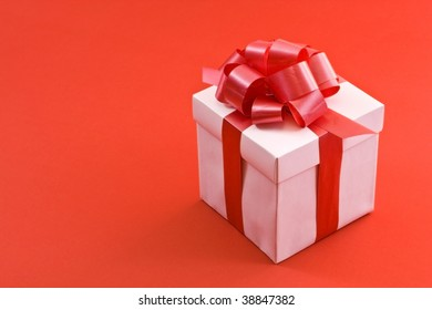A white box tied with a red satin ribbon bow. A gift for Christmas, Birthday, Wedding, or Valentine's day