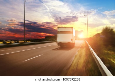 White box truck driving fast on the countryside road against night sky with beautiful sunset