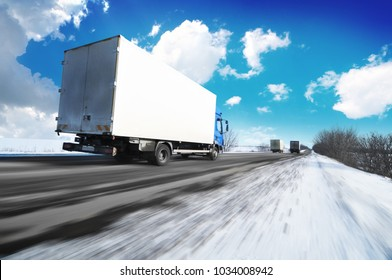White box truck driving fast on the countryside winter road with snow against blue sky with clouds