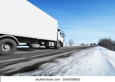 White box truck driving fast on the countryside winter road with snow against blue sky