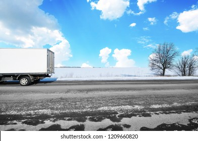 White box truck on the countryside winter road with snow against blue sky with clouds