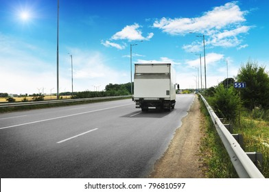 White box truck on the countryside road against blue sky with clouds and sun