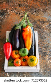 White box with vegetables on a rusty background. Aubergines, bell pepper, tomatoes. Overhead view and copy space.
