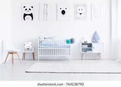 La chambre d'un garçon blanc avec des meubles blancs et des affiches d'animaux sur les murs