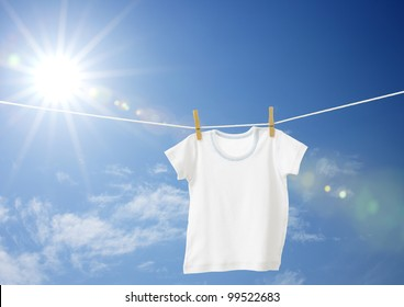 White boys T-shirt on clothes line against blue sky