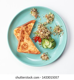 White bread french toast, deep fried in egg batter, served with sprouted peas for breakfast, isolated on white background