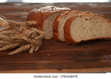 White bread sliced bred with branches of natural wheat on the dark brown wooden background. Organic healthy food