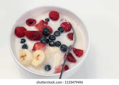 White breakfast bowl of banana, strawberries, blueberries, raspberries, almond milk and cereal. Morning meal of mixed berries, banana, almond milk and organic cereal in a white dish with a spoon.