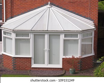 white brick and upvc conservatory at rear of house