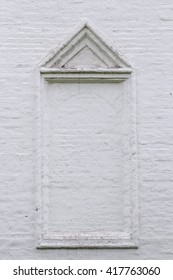 White brick wall with bricked up window, architectural detail triangular pediment