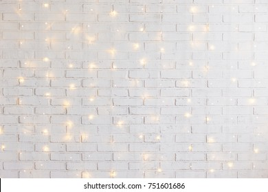 white brick wall christmas background with shiny lights