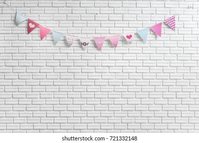 White brick wall decorated by colorful and pink cartoon flags for children or baby shower party event