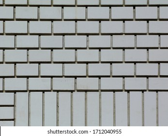 White brick wall elevation detail with deep mortar joints and shadows. running course and part header course. brick pattern concept. smooth white painted texture