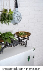 At the white brick wall on the old suitcase are vintage scales with greens. Behind them hang bouquets of herbs and colander.