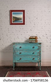 White brick wall with shabby chic vintage turquoise cabinet and hanged painting in living room, with clipping path for the painting