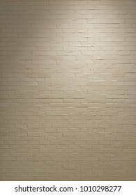 White brick wall texture with lighting on top for background