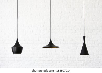 White brick wall and three black, various forms of lamps hanging from the ceiling.