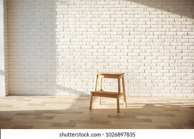 White bricks wall interior background, with sunlight and chair.