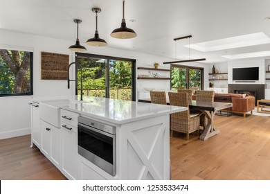White and Bright Kitchen, Dining, and Living Room in New Luxury Home with Open Concept Floor Plan. Kitchen Features Island with Microwave and Farmhouse Sink. Shows View of Trees Through Windows.