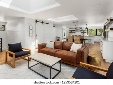 White and Bright Living Room, Dining Room, and Kitchen in New Luxury Home with Open Concept Floor Plan. Features Large Skylights and Barn Doors