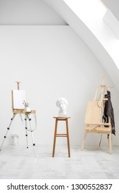 White and bright studio with a window and gray floor. Workspace of the artist. Easel, canvases and plaster figures for learning to draw. Conceptual interior without people.