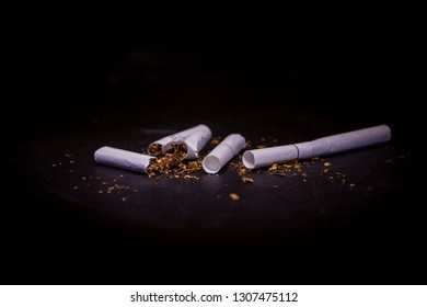 White broken cigarettes on black background. Smoking is injurious to health.