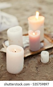 white and brown candles on sand
