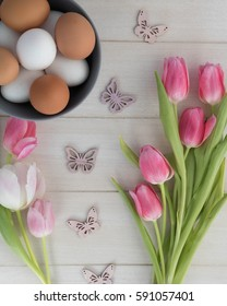 white and brown easter eggs in bowl with pink and white tulips and butterflies on wooden background