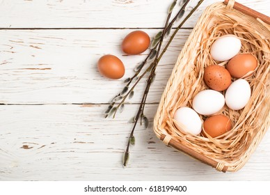 White and brown eggs in the basket on the table. Easter. Top view. Copy space