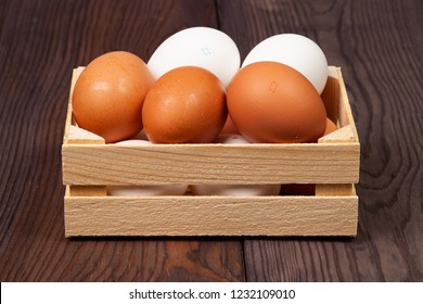 White and brown eggs in wooden crate on wooden background. Close-up view.