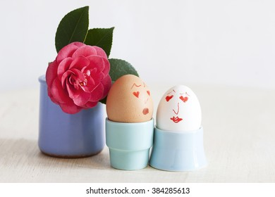 White and brown hen eggs with faces painted on in light blue egg cups.