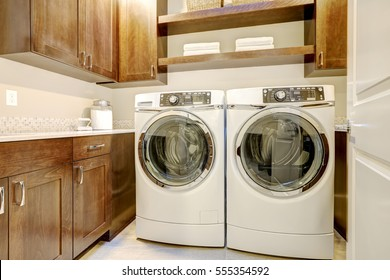 White and brown laundry room features modern appliances placed under shelves and cabinets. Northwest, USA