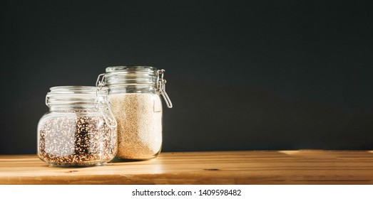 White and brown raw organic quinoa in glass storage containers. Healthy cooking, clean eating, zero waste concept. Balanced dieting food. Copy space. Banner with copy space.