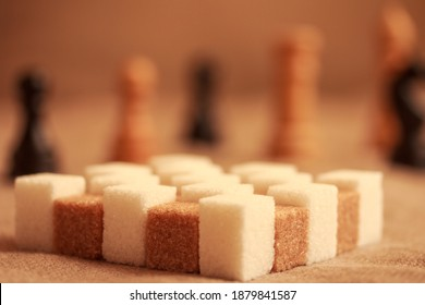 White and brown sugar cubes in form of a chessboard and chessmen in the background .  Closeup. Bokeh. Copy space