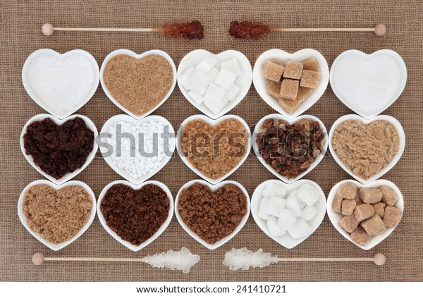 White and brown sugar selection in heart shaped bowls with crystal lollipop sticks over hessian background.