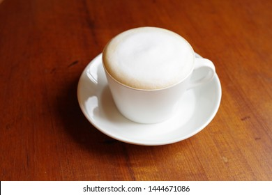 White bubble of cappuccino poured into a cup