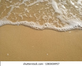White bubbles of wave crash the sandy beach , for background
