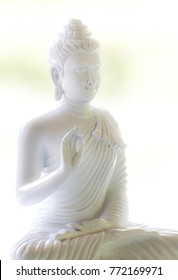 White Buddha with natural light in white scene.