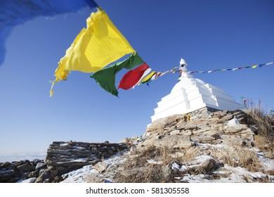 White Buddhist stupa with colorful flags. Ogoi island. Baikal landmark. Russia