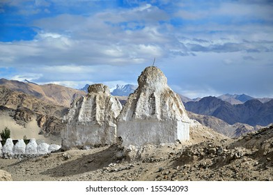 White buddhist stupas and Himalayas mountains on the background in valley near Leh, Ladakh, India