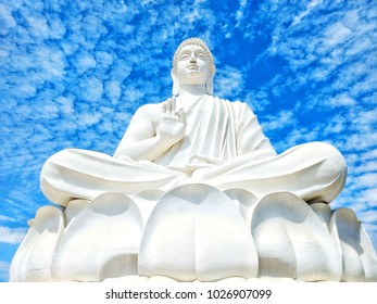 White Budha Statue infornt of a beautiful blue sky