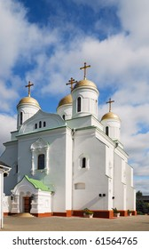 White building with golden crosses is photographed against the cloudy sky. Zymne's castle-convent is one of the most ancient orthodox church. It was found by Prince Vladimir in the 10th century. - Shutterstock ID 61564765