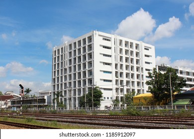 A white building with rail tracks in front of the building.