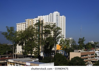 White building surrounded by trees,background is the blue sky in thailand .