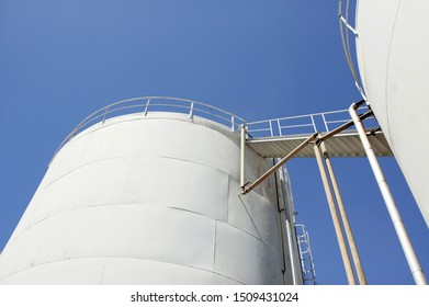 White bulk storage tank for oil low angle against blue skies