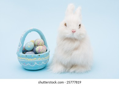 White bunny rabbit with a basket of eggs sitting on a blue background, bunny