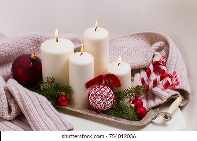 White burning advent candles with christmas decorations and knitted blanket
