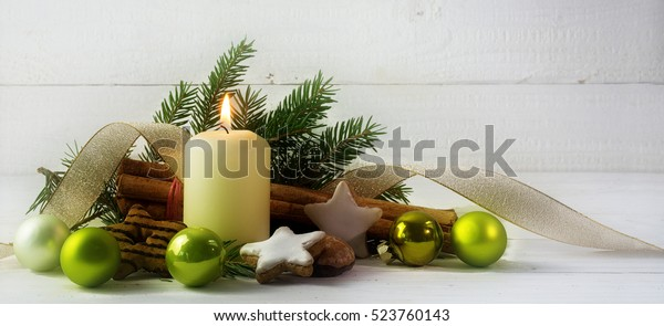 White burning candle with christmas decoration, fir tree, cookies, green baubles and golden ribbon, against rustic white wood with generous copy space, panorama, selected focus, narrow depth of field